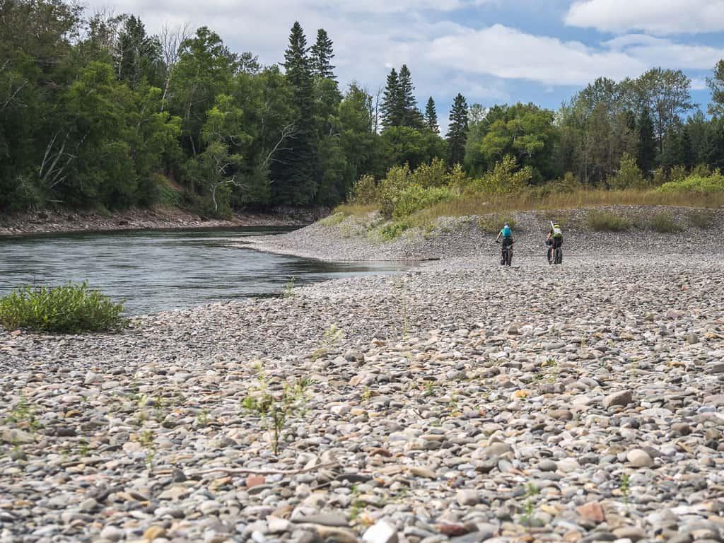 Deux filles sont en fatbike sur les berges de la rivière Bonaventure pour aller pêcher à la mouche