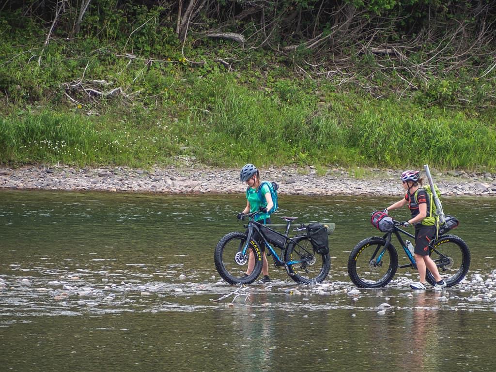 Deux filles faisant une approche en fatbike Panorama Chic-Chocs pour aller pêcher à la mouche sur la Bonaventure