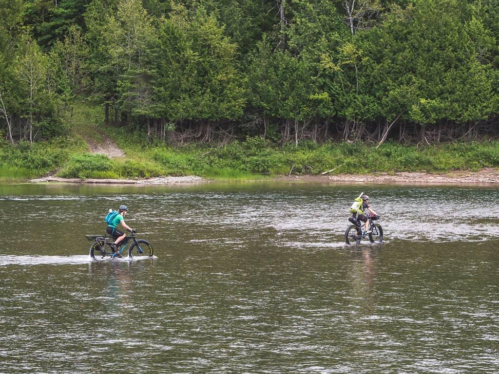 Deux filles traverse une rivière en fatbike Panorama pour aller pêcher à la mouche