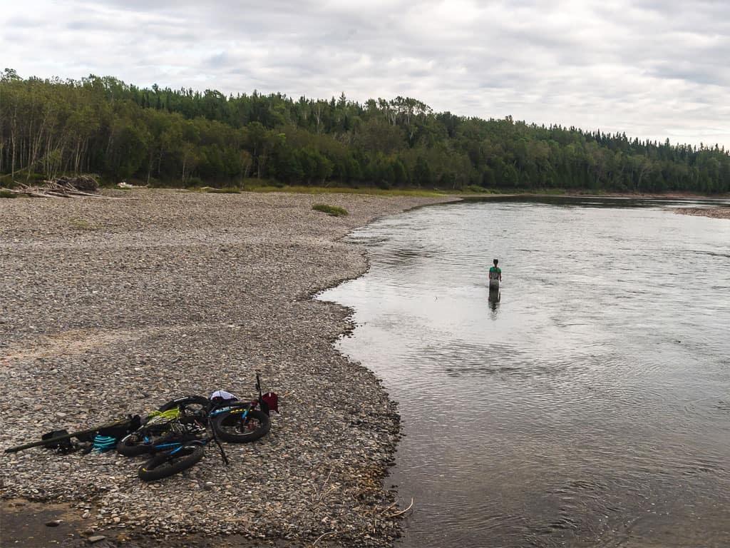 Une fille pêche à la mouche dans la Bonaventure après avoir fait l'approche en fatbike