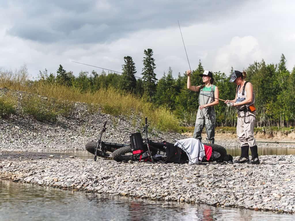 Deux filles se préparent à aller pêcher à la mouche sur la rivière Bonaventure après une approche en fatbike