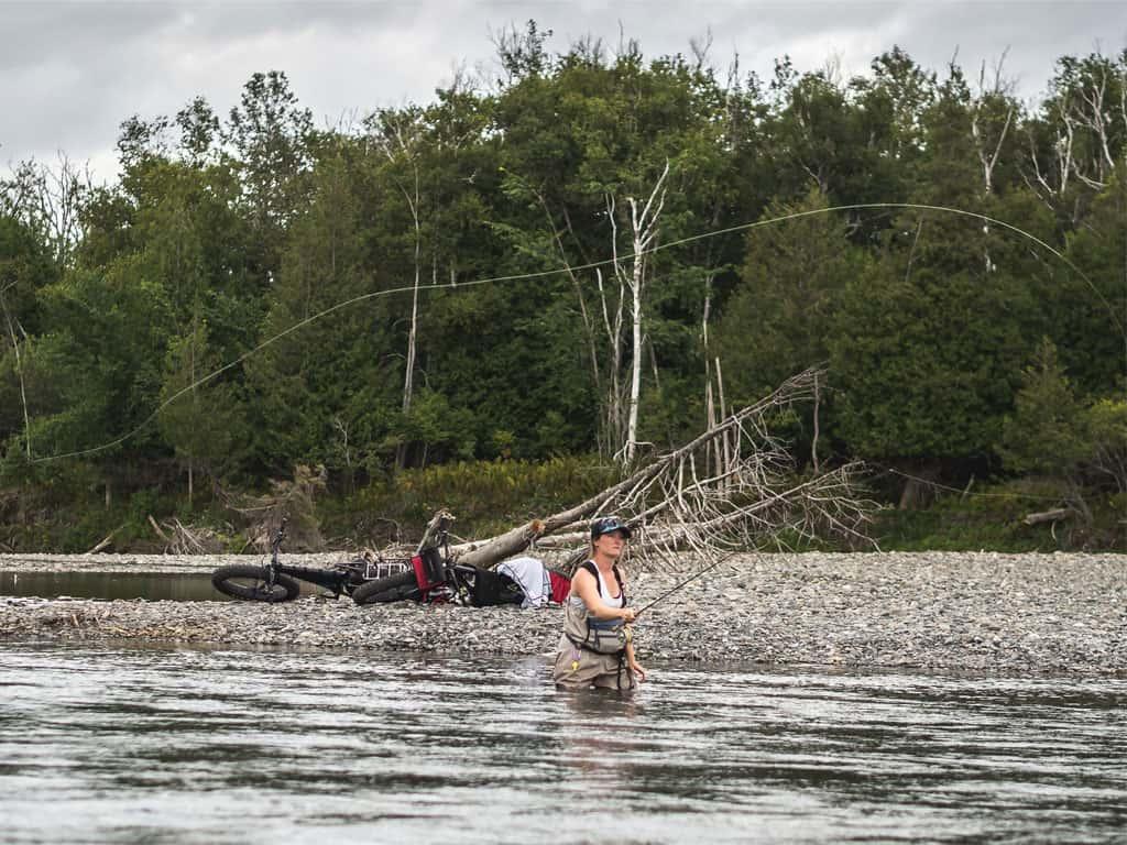 Un lancer de pêche à la mouche sur la rivière Bonaventure par une fille et des fatbike Panorama en arrière plan