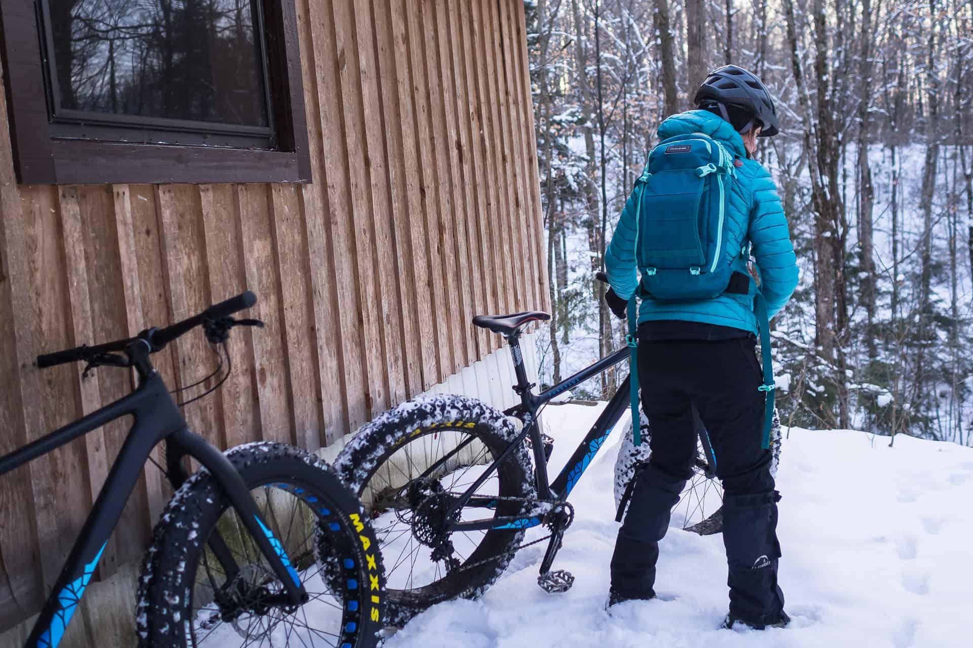 Une fille prend son fatbike Panorama Cycles qui était appuyé à un refuge lors d'une sortie d'hiver