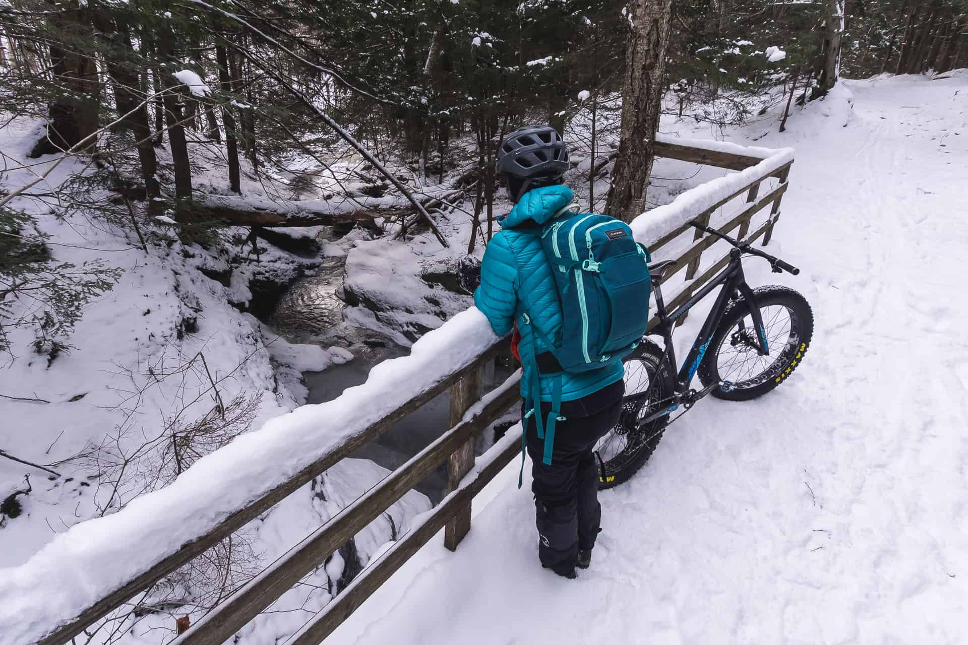 Une fille vêtue d'une doudoune regarde le ruisseau gelé lors d'une pause de sa randonnée de fatbike hivernale