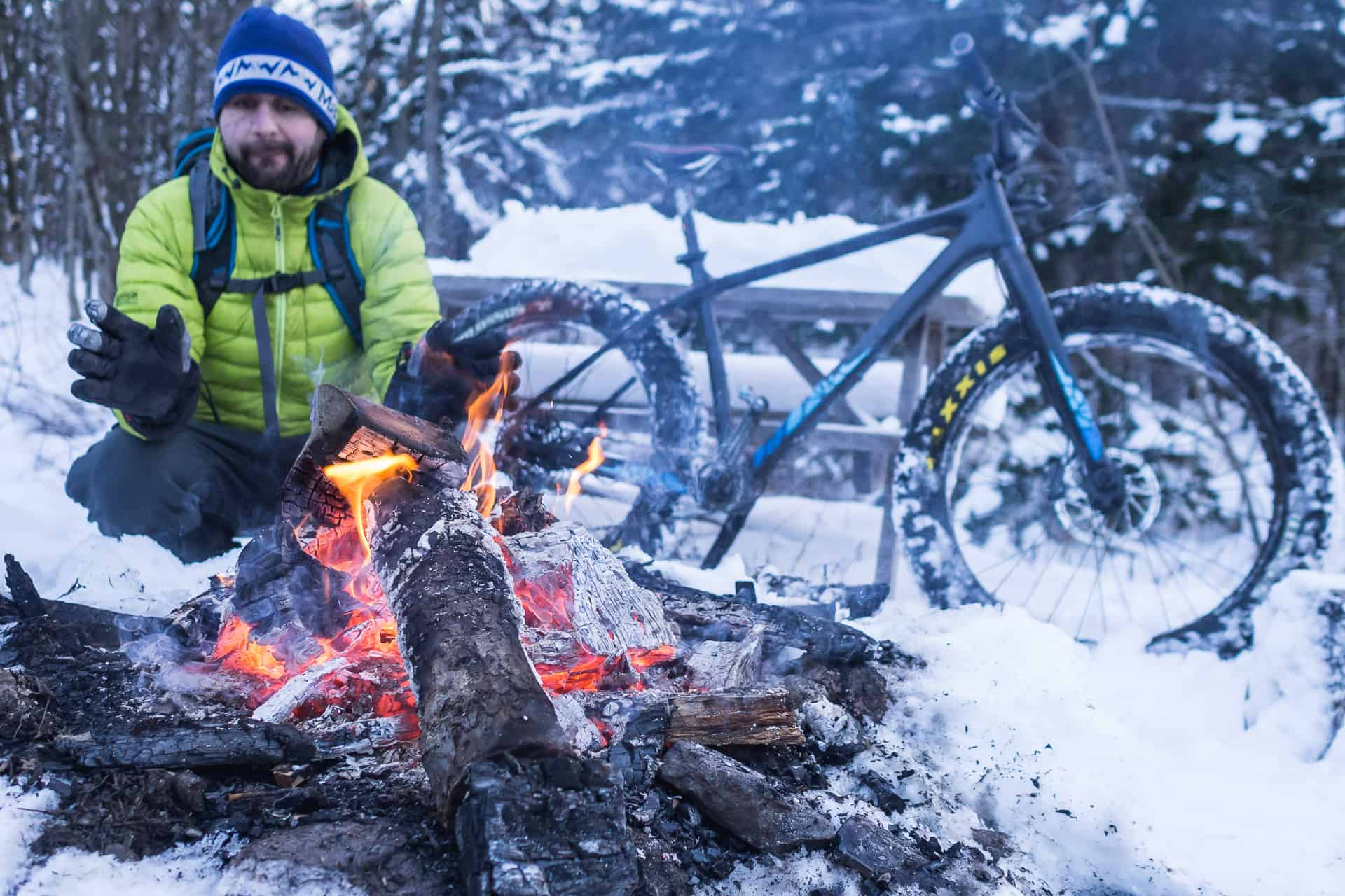 Un homme se réchauffe les mains auprès d'un feu de camp après une sortie d'hiver en fatbike