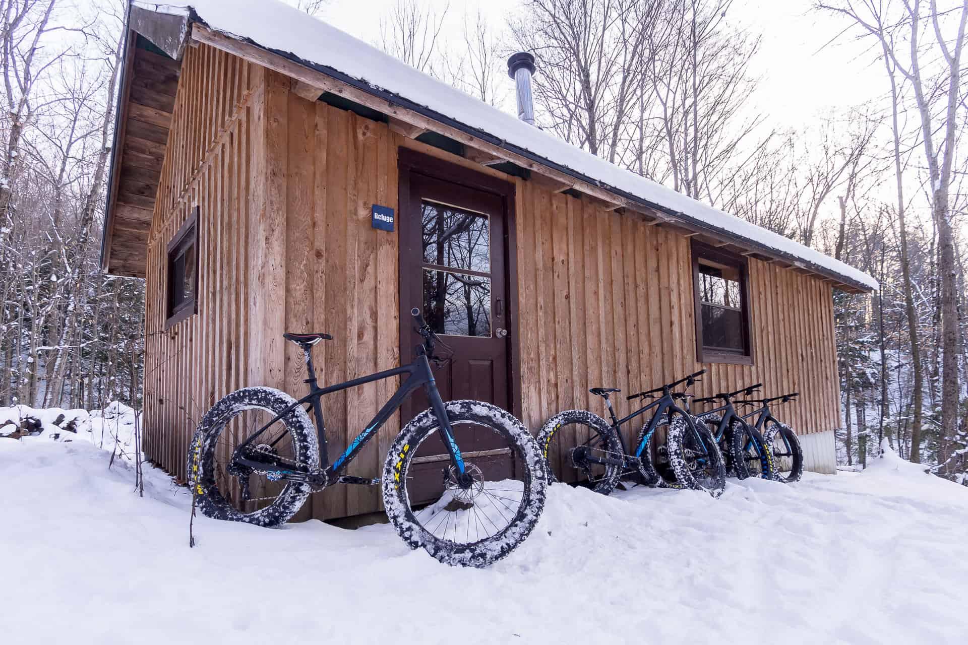 Quatre fatbikes Panorama Chic-Chocs appuyés à un refuge dans un décors d'hiver