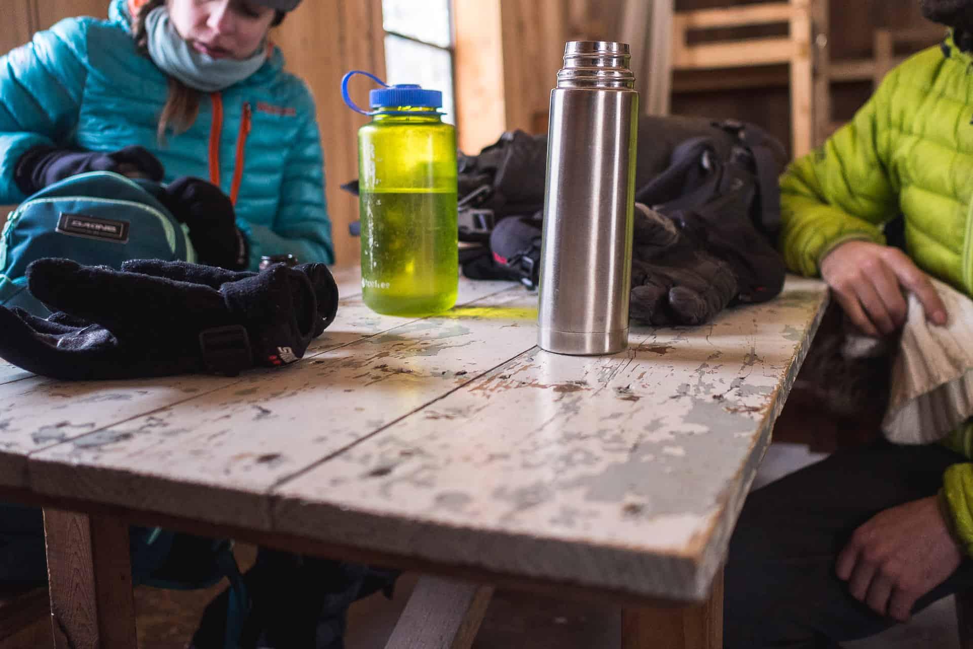 Termos et bouteille nalgene dans un refuge lors d'un arrêt de l'expédition hivernale