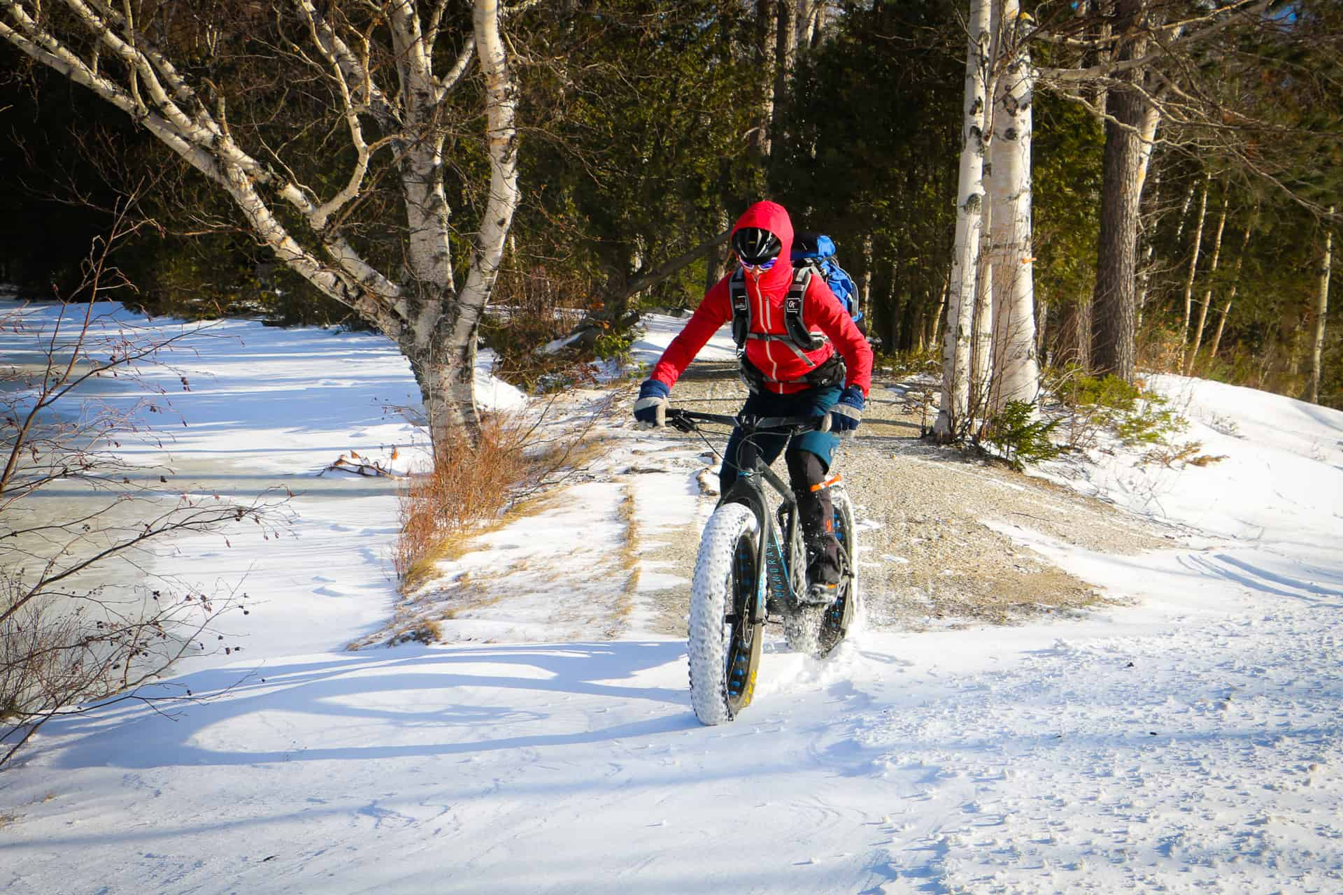 A lady climbing a snowy road on a fat bike