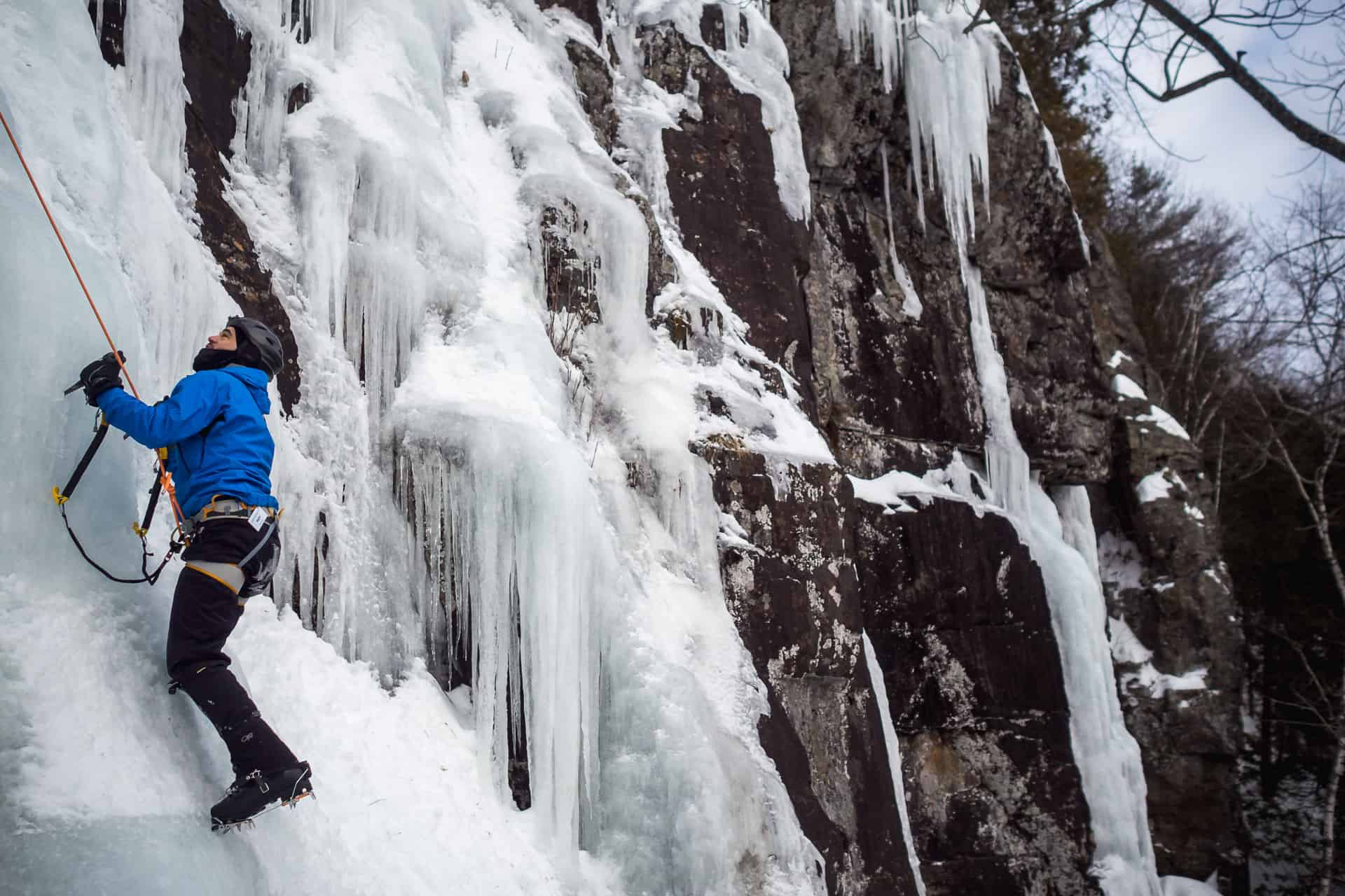 A man climb a frozen waterfall after a fatbike approach