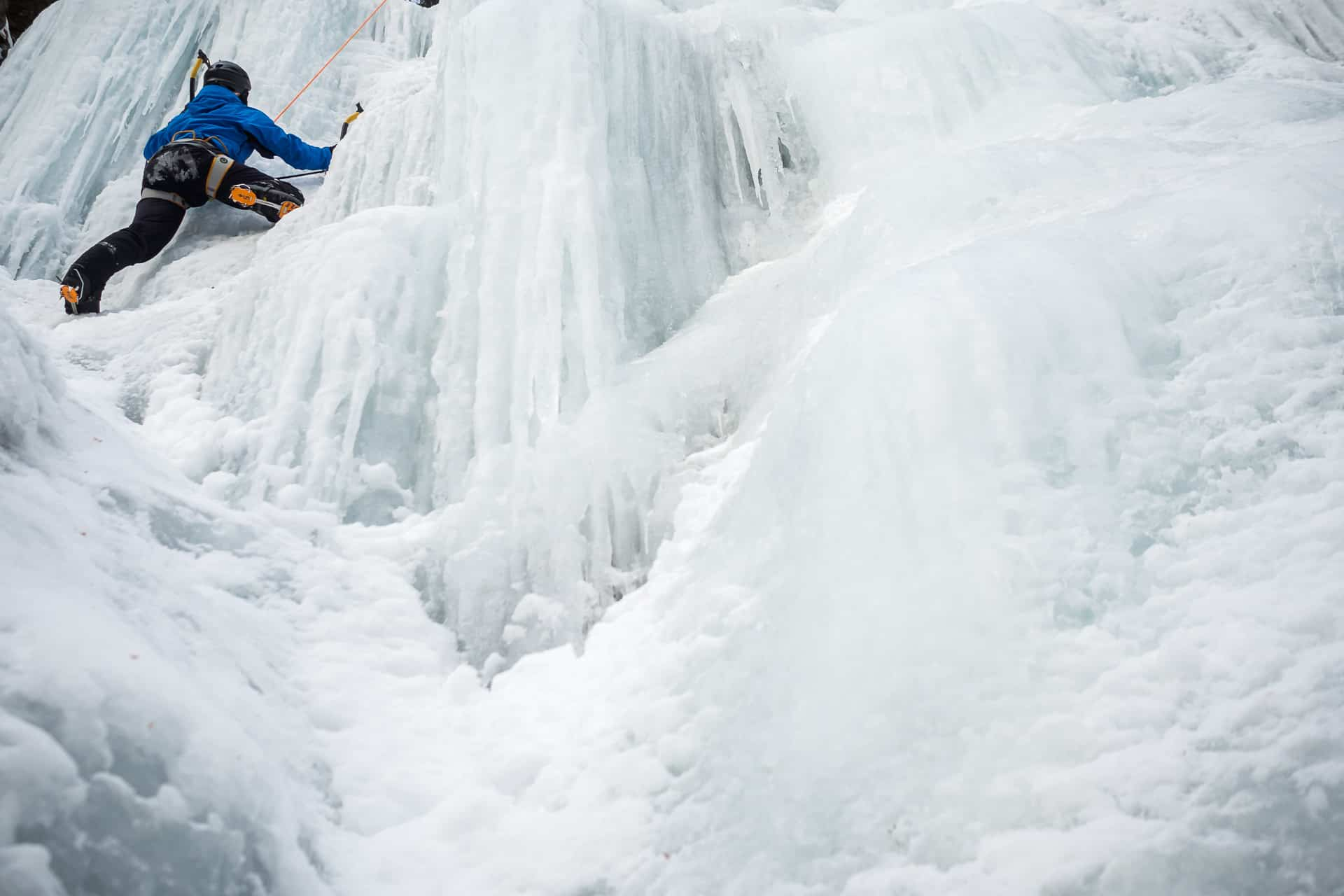 A man ice climbing on a waterfall