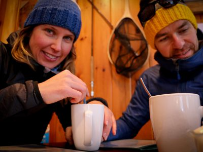 Afemale and a male smiling and drinking coffee after a fatbike ride
