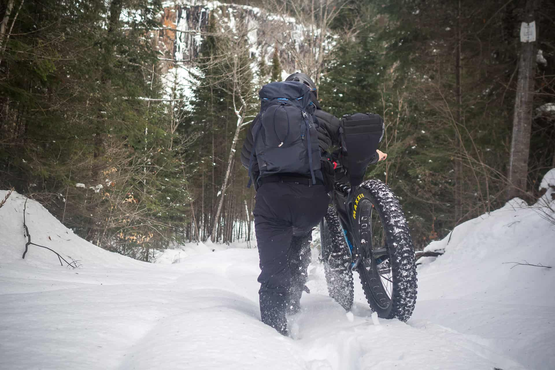A man pushing his fatbike in deep snow