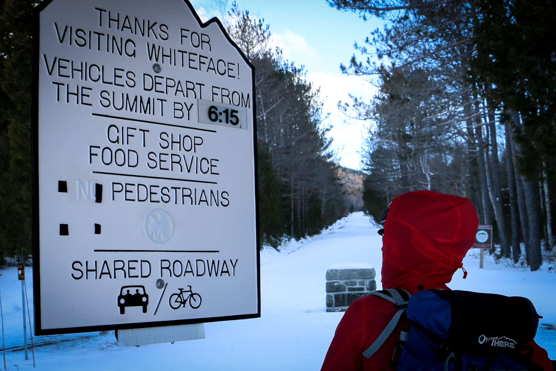 A cyclist starring at the sign at the bottom of the memorial highway going up whiteface mountain