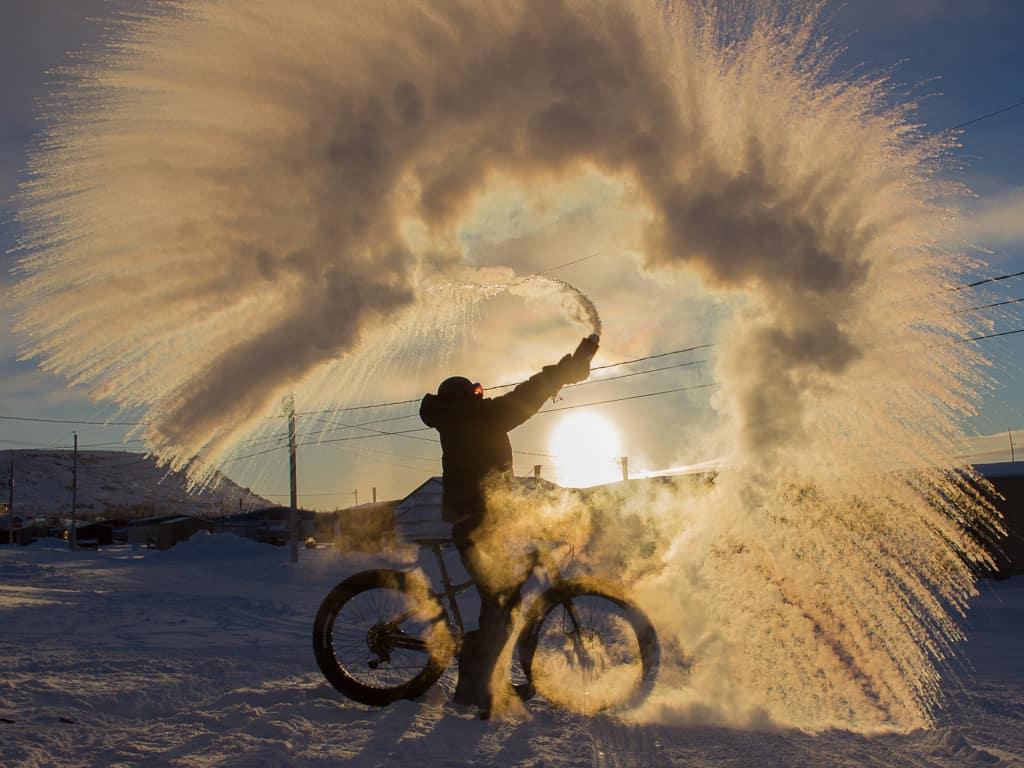 Marie-Andrée Fortin dans le Nord du Québec au froid lançant de l'eau dans les airs.